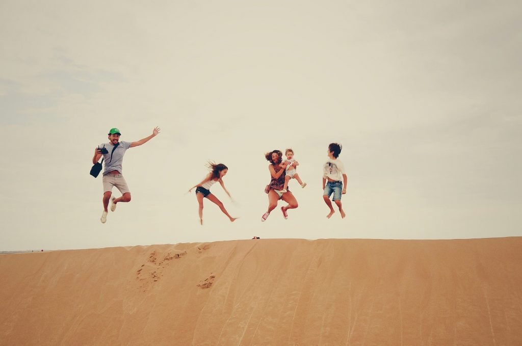 Family playing on a sand dune.