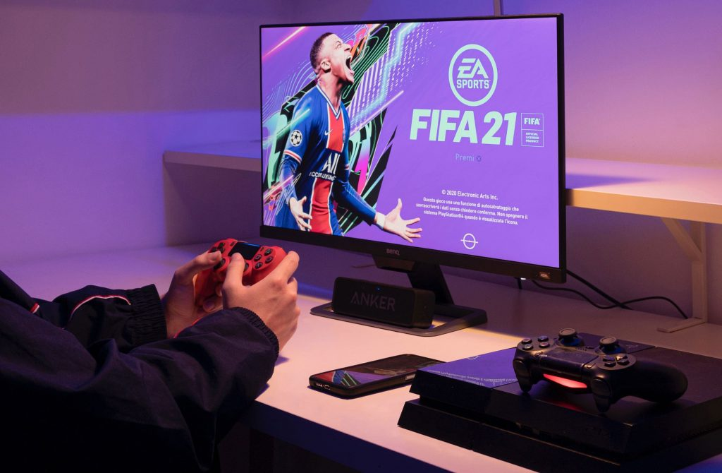 Man playing FIFA 21 on a Playstation.