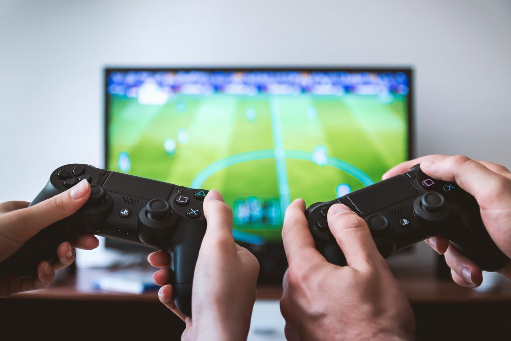 Two people playing FIFA on a TV.