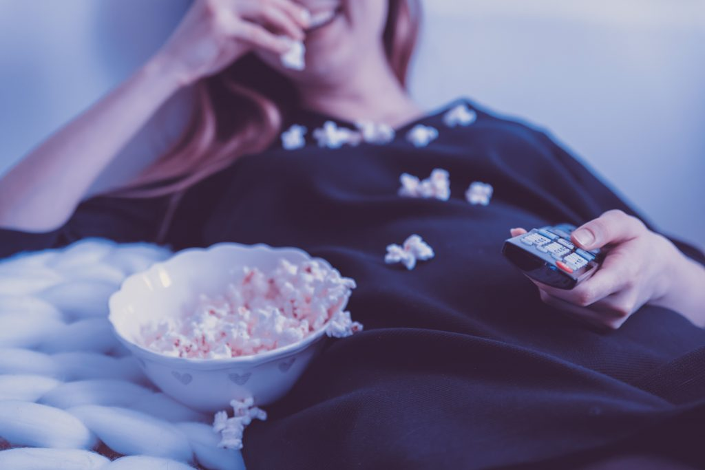 Woman watching TV eating popcorn.